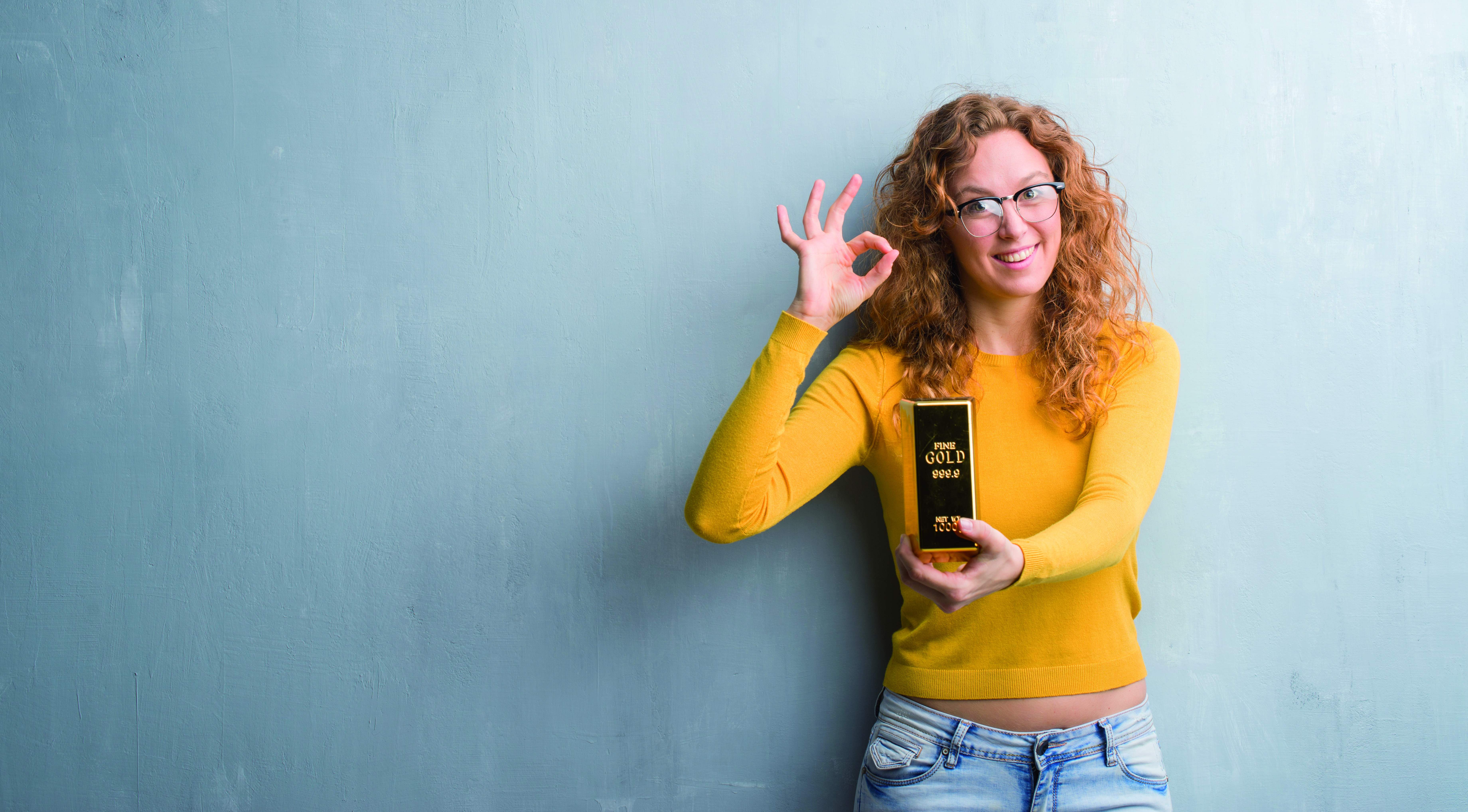 Young Redhead Woman Over Grey Grunge Wall Holding Gold Ingot Doing Ok Sign With Fingers, Excellent Symbol